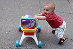 Austin 12 mos. old outside, full length, walking pushing wheeled toy cart