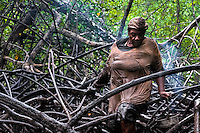 A Colombian woman climbs over the root of a tree while searching for shellfish in the mangrove swamps on the Pacific coast, Colombia, 12 June 2010. Deep in the impenetrable labyrinth of mangrove swamps on the Pacific seashore, hundreds of people struggle everyday, searching and gathering a tiny shellfish called 'piangua'. Wading through sticky mud among the mangrove tree roots, facing the clouds of mosquitos, they pick up mussels hidden deep in mud, no matter of unbearable tropical heat or strong rain. Although the shellfish pickers, mostly Afro-Colombians displaced by the Colombian armed conflict, take a high risk (malaria, poisonous bites,...), their salary is very low and keeps them living in extreme poverty.