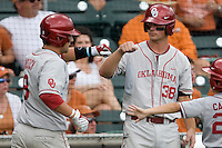 Third baseman Garrett Buechele #38 of the Oklahoma Sooners greets teammate Evan Mistich #9 after he scored against the Texas Longhorns in NCAA Big XII baseball on May 1, 2011 at Disch Falk Field in Austin, Texas. (Photo by Andrew Woolley / Four Seam Images)