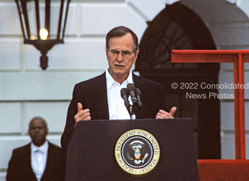 United States President George H.W. Bush makes remarks as he and first lady Barbara Bush kick-off the Great American Workout Month with Arnold Schwarzenegger and US Secretary of Health and Human Services Louis Sullivan on the South Lawn of the White House in Washington, D.C. on May 1, 1990.<br /> Credit: Arnie Sachs / CNP