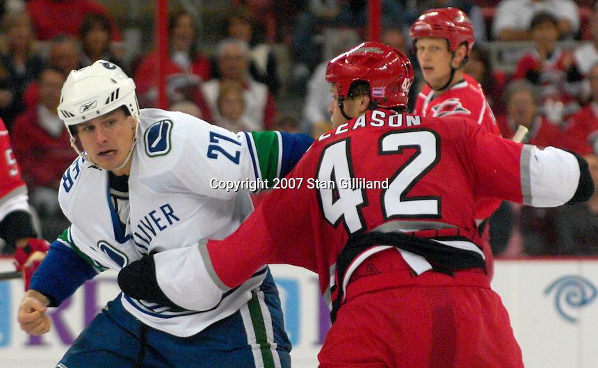 Carolina Hurricanes defenseman Tim Gleason and the Vancouver Canucks' Brad Isbister square off during their game Monday, Oct. 22, 2007 in Raleigh, NC. The Hurricanes won 3-1.