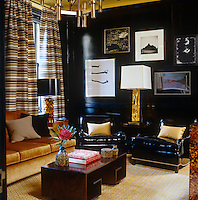 A pair of black patent leather club chairs against the black panelled wall of the library
