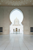 The Sheikh Zayed Grand Mosque in Abu Dhabi, also known as the White Mosque, is a masterpiece of architecture and craftsmanship. View from the entrance arch towards the huge dome above the main prayer halls.