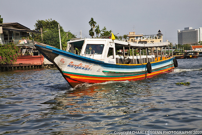 Colorful boats ply the Chao Phraya river  through the heart of Bangkok.