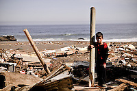 Chile, Aftermath of the tsunami in the area of Consitucion.Cristóbal Vásquez Vera (7) collecting woods of his room.