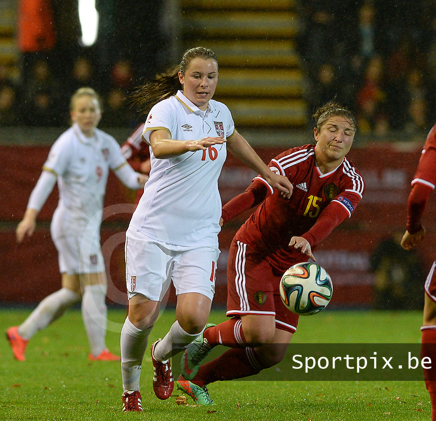 20151130 - LEUVEN ,  BELGIUM : Belgian Sara Yuceil (r) pictured in a duel with Serbian Dina Blagojevic (left) during the female soccer game between the Belgian Red Flames and Serbia , the third game in the qualification for the European Championship in The Netherlands 2017  , Monday 30 November 2015 at Stadion Den Dreef  in Leuven , Belgium. PHOTO DAVID CATRY