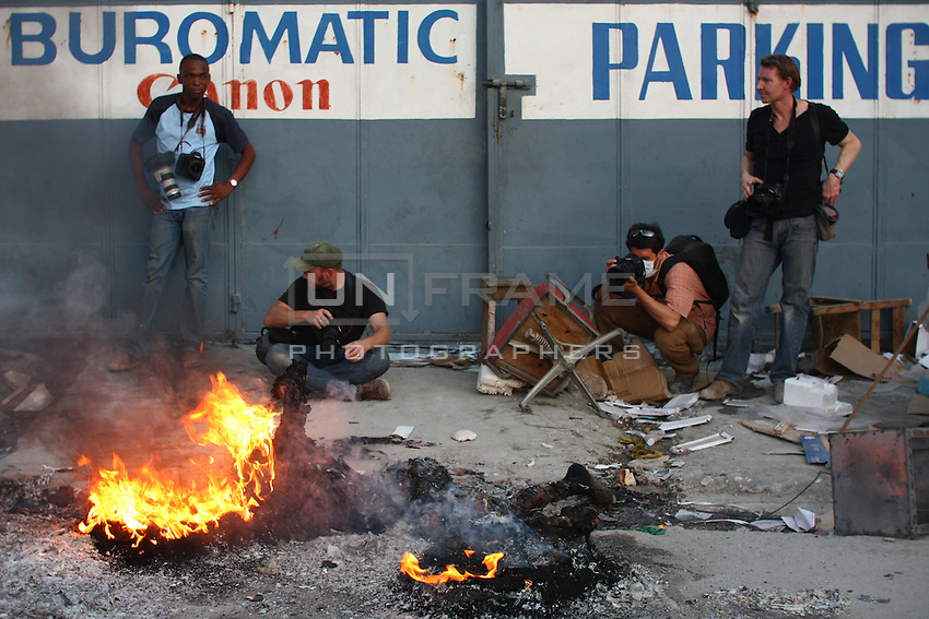 Photographers are seen near a burning body in downtown Port-au-Prince days after the January 10th earthquake that struck the island killing hundreds of thousands of people. Haiti, Jan. 20, 2010. (photo by Nick Kozak / UnFrame )