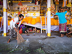 14 JULY 2016 - UBUD, BALI, INDONESIA: A woman cleans the pavement in front of the alter that holds her family member who will be cremated in a mass cremation Saturday. Local people in Ubud exhumed the remains of family members and burned their remains in a mass cremation ceremony Wednesday. Thursday was spent preparing for Saturday's ceremony that concludes the cremation. Almost 100 people will be cremated and laid to rest in the largest mass cremation in Bali in years this week. Most of the people on Bali are Hindus. Traditional cremations in Bali are very expensive, so communities usually hold one mass cremation approximately every five years. The cremation in Ubud will conclude Saturday, with a large community ceremony.     PHOTO BY JACK KURTZ