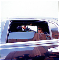 Man in suit looking through limousine window at woman inside<br />