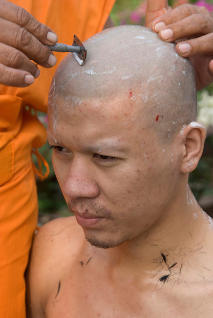 Young man gets his head shaved before he is ordained as a Buddhist Monk