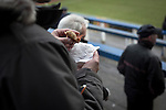 A home supporter in the Shed eating a pie as Greenock Morton (in hoops) take on Stranraer in a Scottish League One match at Cappielow Park, Greenock. The match was between the top two teams in Scotland's third tier, with Morton winning by two goals to nil. The attendance was 1,921, above average for Morton's games during the 2014-15 season so far.