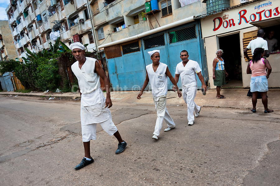 """Cuban cooks walk out of the cafeteria in the apartment block in Alamar, a public housing periphery of Havana, Cuba, 9 February 2011. The Cuban economic transformation (after the revolution in 1959) has changed the housing status in Cuba from a consumer commodity into a social right. In 1970s, to overcome the serious housing shortage, the Cuban state took over the Soviet Union concept of social housing. Using prefabricated panel factories, donated to Cuba by Soviets, huge public housing complexes have risen in the outskirts of Cuban towns. Although these mass housing settlements provided habitation to many families, they often lack infrastructure, culture, shops, services and well-maintained public spaces. Many local residents have no feeling of belonging and inspite of living on a tropical island, they claim to be """"living in Siberia""""."""