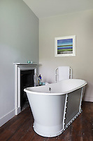 A simple bathroom with a free-standing tub with visable rivets