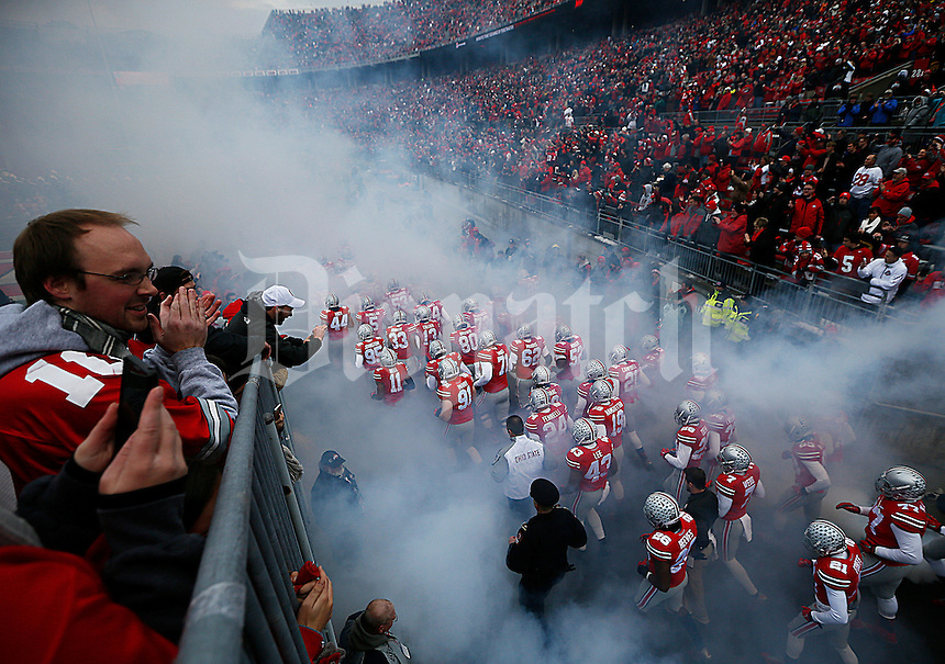 The Ohio State Buckeyes run on to the field before the college football game between the Ohio State Buckeyes and the Indiana Hoosiers at Ohio Stadium in Columbus, Saturday afternoon, November 22, 2014. As of half time the Ohio State Buckeyes led the Indiana Hoosiers 14 - 13. (The Columbus Dispatch / Eamon Queeney)