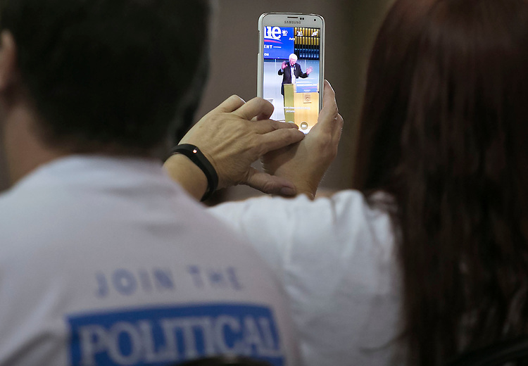 "UNITED STATES - August 16: A woman uses her smart phone to take a photograph as Sen. Bernie Sanders, D-Vt., speaks at the Loras College Athletic and Wellness Center in Dubuque, Iowa, on Sunday, August 16, 2015. The ""town meeting,"" was the fourth campaign event of the day for Sanders. (Photo By Al Drago/CQ Roll Call)"