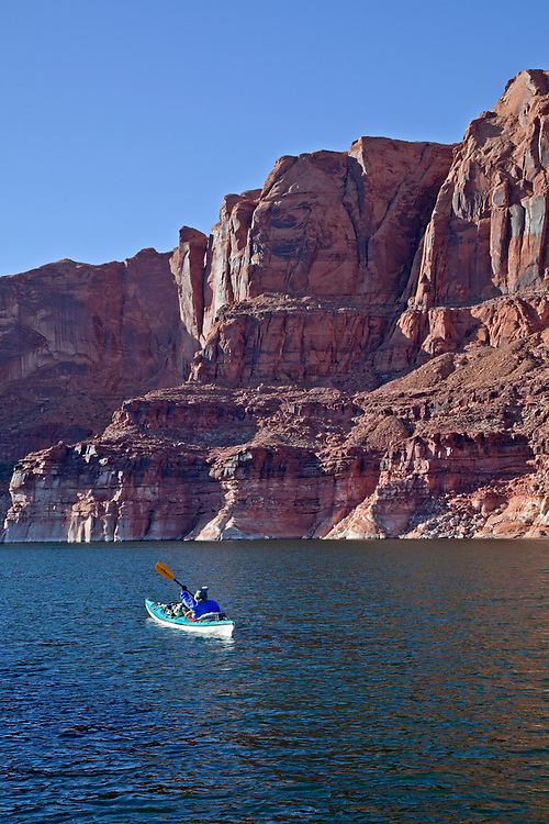 Jacque Miniuk paddles along unnamed sheer sandstone cliffs near mile 114 on Lake Powell in the Glen Canyon National Recreation Area, Utah