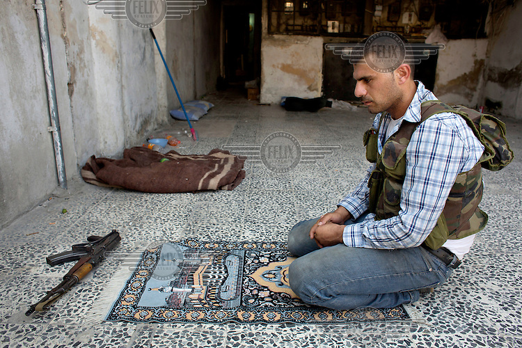A rebel Free Syrian Army (FSA) fighter prays near the front lines of Salaheddin in Aleppo.