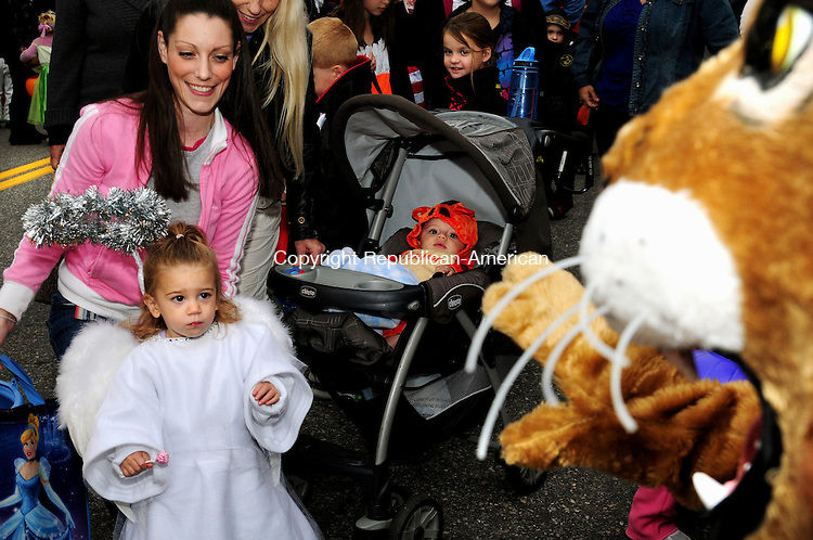 TORRINGTON, CT, 27 OCT 12-102712AJ01- Mikayla Barone, 21 months, of Morris, who was with her mom, Jessy Barone,  shies away from John Liuiza dressed at a lion at Torrington's Trunk or Treat on Main Street Saturday evening. The event, planned by the Parks and Recreation Department and co-sponsored by the Lions Club, and the Torrington Municipal & Teachers Federal Credit Union drew hundreds of children and their parents downtown for Halloween festivities. Austin Barone, 7 mo., is in the carriage Alec Johnson/ Republican-American