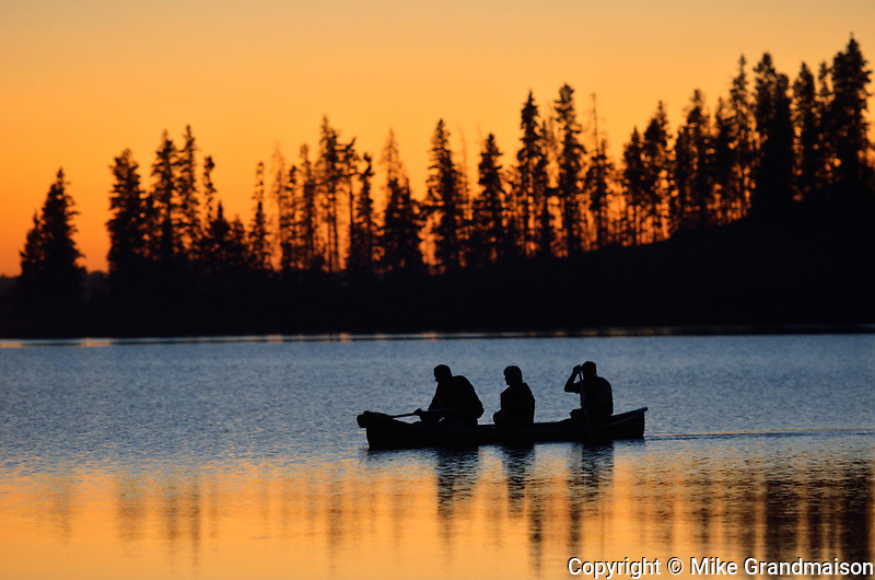 Family canoeing on Astotin Lake at sunset<br />