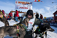 2010 third-place finisher Jeff King gets kisses from one of his lead dogs at the Nome finish line