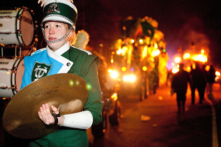 A cymbal player for the Tulane University marching band, with flambeau carriers behind her, at Le Krewe d'Etat parade in New Orleans on February 12, 2010.  While Le Krewe d'Etat is a relative newcomer to Mardi Gras, having first paraded in 1998, its practices are very traditional, including riders on horseback, flambeau carriers, and a heavy dose of satire on its floats as it parades on its uptown route.