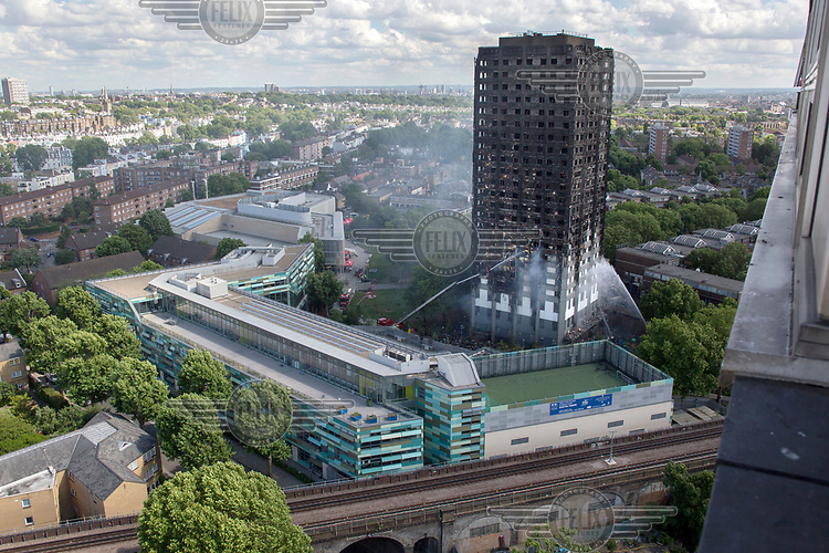 Fire crews spray water into the charred remains of Grenfell Tower in North Kensington following the devastating fire that swept up the 24 storey building in the early hours of Wednesday, 14th June killing at least 79 people and leaving many more without homes or possessions.
