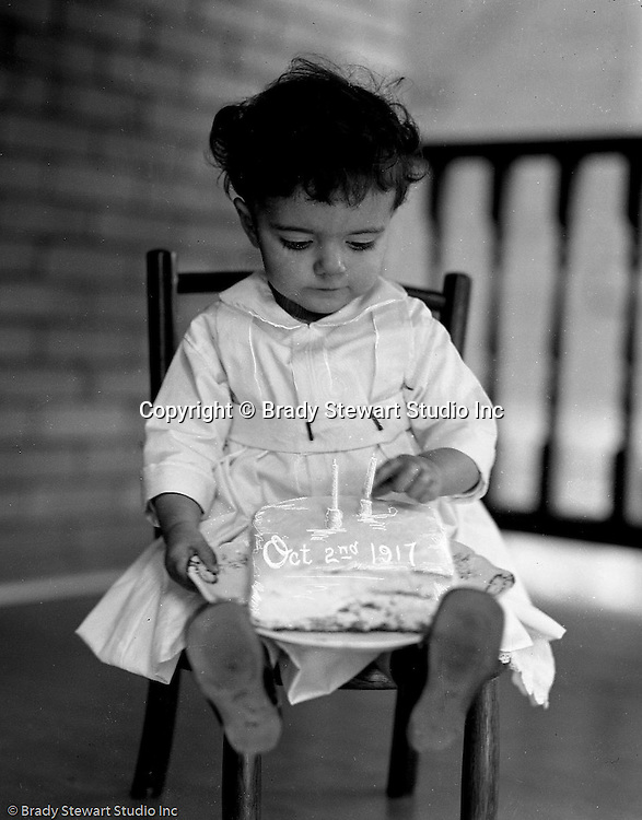 Wilkinsburg PA:  Helen Stewart celebrating her second birthday with a cake on front porch - 1917.
