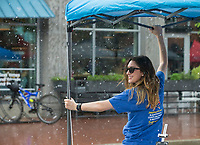 NWA Democrat-Gazette/BEN GOFF @NWABENGOFF<br /> Jessica Benford with Jake's Fireworks holds down the company's tent Friday, June 7, 2019, during a brief downpour at First Friday on the Bentonville square. This month the theme was 'Living Local' with a focus on local history, food, music and businesses.