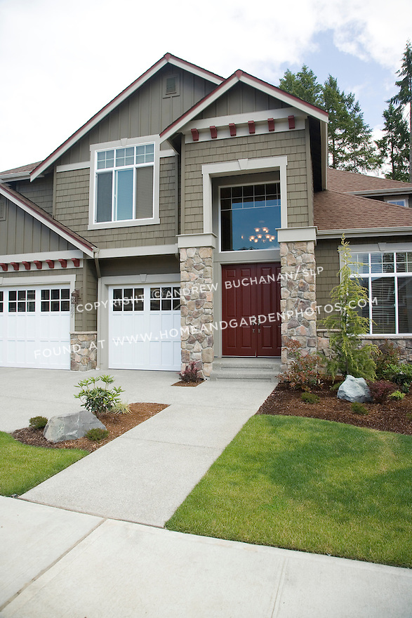 The front, shingled facade and dark red front door of a large, two story, 2-story, 4+BR bedroom builder spec home in a suburban development near Olympia, WA.