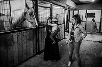 Suhad Abu Shihada, 31, holds her daughter, <br /> Sara Abu Shihada, 2, as her sister, Maisa Muthafar, 17,  looks on as they visit horses in the stable at the Al-Badiya al-Maqdisi Club on June 12, 2016 in the neighborhood of Tur, East Jerusalem. <br /> Photo Daniel Berehulak for the New York Times
