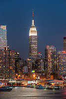 The Empire State Building and surrounding buildings at dusk, with the Hudson River lit by the light of the full moon, as seen from Weehawken, New Jersey