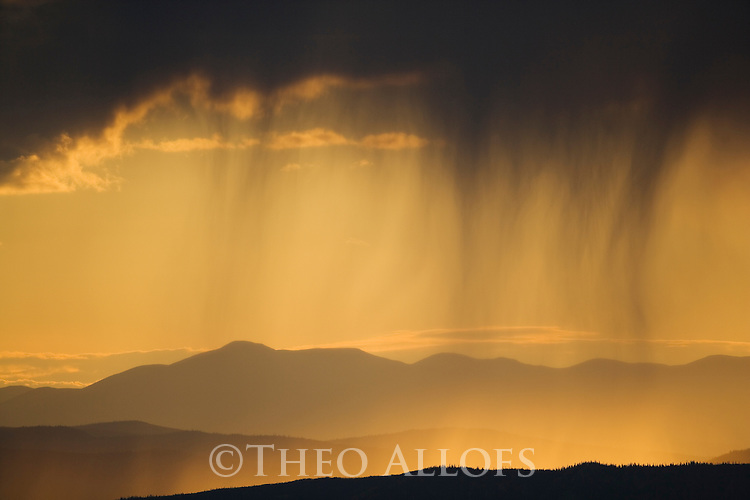 """View onto successive hills along the """"Top of the World Highway""""  between Dawson City/Yukon and Tok/Alaska; rain clouds at horizon, backlit scene at sunset"""