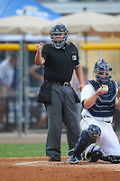 Umpire J.C. Velez strike call as catcher Kade Scivicque (28) throws the ball back to the pitcher during a game between the Lakeland Flying Tigers and Jupiter Hammerheads on March 14, 2016 at Henley Field in Lakeland, Florida.  Lakeland defeated Jupiter 5-0.  (Mike Janes/Four Seam Images)
