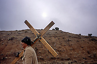 Fred Garcia, 68, of Albuquerque, N.M., carries a cross to the Santuário de Chimayó in northern New Mexico on Good Friday. Thousands of pilgrims make a pilgrimage to the 190-year-old shrine every Easter as an expression of faith, a connection to old Hispanic roots and in hopes of the miracles reputed to occur there. Garcia has been carrying the same cross for 25 years.<br />