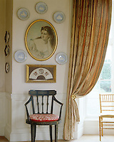 A painting of a young woman is accompanied by a plate display on the wall of the drawing room