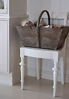 A wooden basket full of Christmas treats sits on this painted kitchen chair