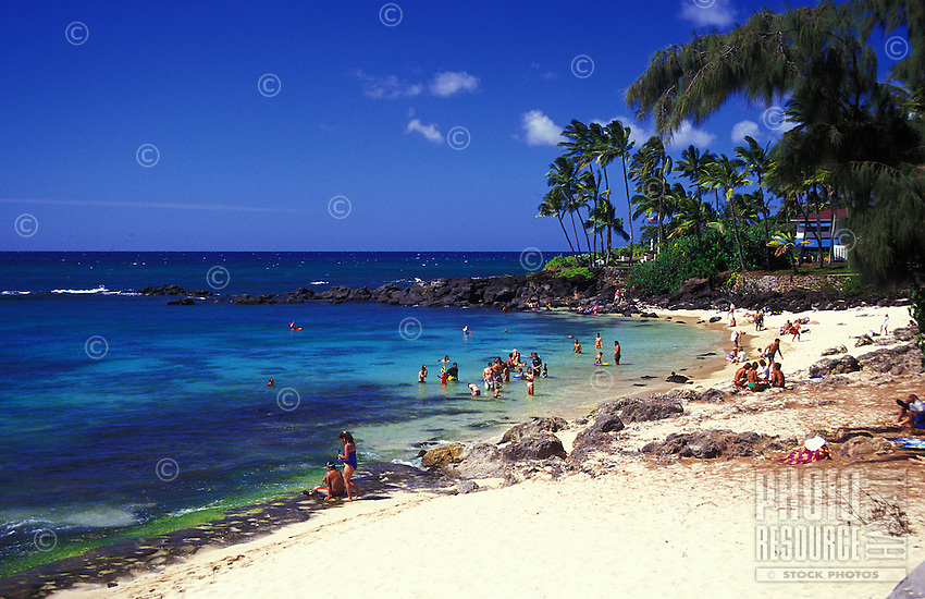 People at laniakea beach, a popular spot where turtles rest on the beach and swim along shoreline with tourists