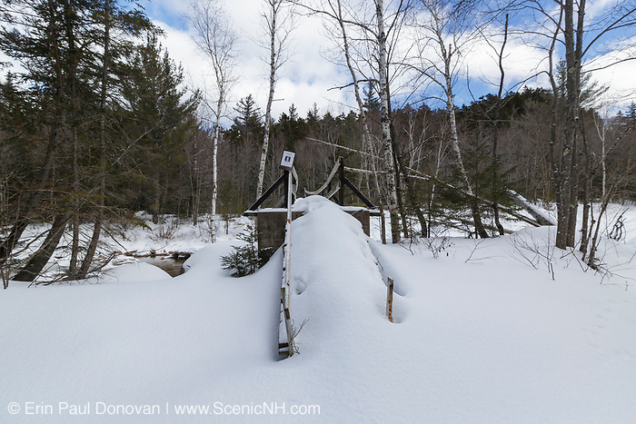The Thoreau Falls Trail bridge at North Fork Junction in the Pemigewasset Wilderness of New Hampshire during the winter months on a Monday morning after weekend hiker traffic to the White Mountains. This bridge spans the East Branch of the Pemigewasset River. And this photo shows that no one has used the bridge in days (that is not new snow).