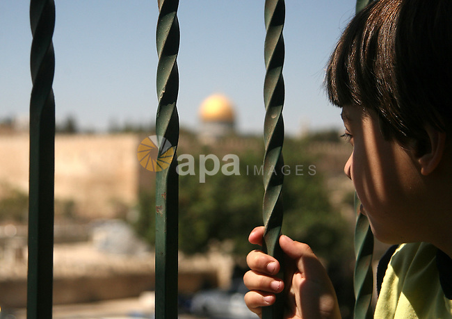 A Palestinian boy looks at the Dome of the Rock mosque as Israeli police blocks the access to Al-Aqsa Mosque, outside the Old City walls in East Jerusalem on September 18, 2015. Israel deployed hundreds of extra police around the Old City of Jerusalem on Friday to bar young Muslim men from prayers at the Al-Aqsa mosque site after Palestinian leaders called for a 'day of rage' to protest at new Israeli security measures. Photo by Mahfouz Abu Turk