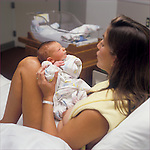 Young new mother talking to her newborn son in the hospital maternity ward, parenting