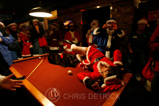 Salt Lake City,Ut--12/16/05--7:46:29 PM- .On top of a pool table, Julie Hayes aka &quot;Mistrez Clawz&quot; flirts with a Santa Clause at O'Shucks Bar during the 10th annual Santa Pub Crawl. More than 150 would-be Santas spiced up the town and spread seasonal cheer on their sudsy tour of Salt Lake pubs..<br />