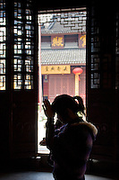 Worshipper praying at the Jade Buddha Temple, Shanghai, China