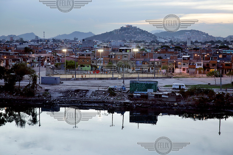 A floodlit sportsfield and housing in Favela da Mare.