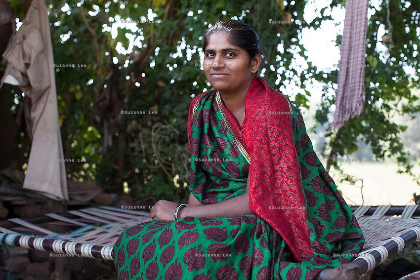 Pinki Khristi, 28, sits for a portrait at her farm house in Anand, Gujarat, India on 9th December 2012. Pinki's sister-in-law had convinced her to become a surrogate together with her in 2008 and Pinki has since done 2 surrogacies. While Pinki and her husband Dhiraj used to make 2000-5000 rupees per month from farming and as labourers, she had made over 850,000 from both her surrogacies and had bought land, buffaloes and saved 320,000 rupees in a fixed deposit. Photo by Suzanne Lee / Marie-Claire France