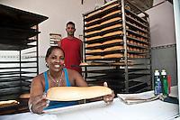 L'Avana, panificio, panettiera sorridente mostra forma di pane, sullo sfondo fornaio e pane sfornato