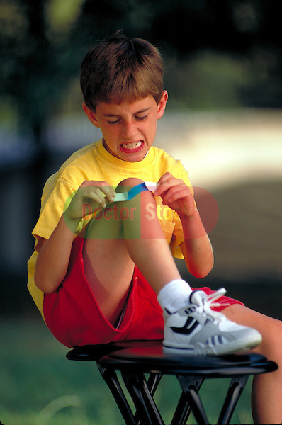 grimacing young boy applying a band-aid, bandaging injured knee