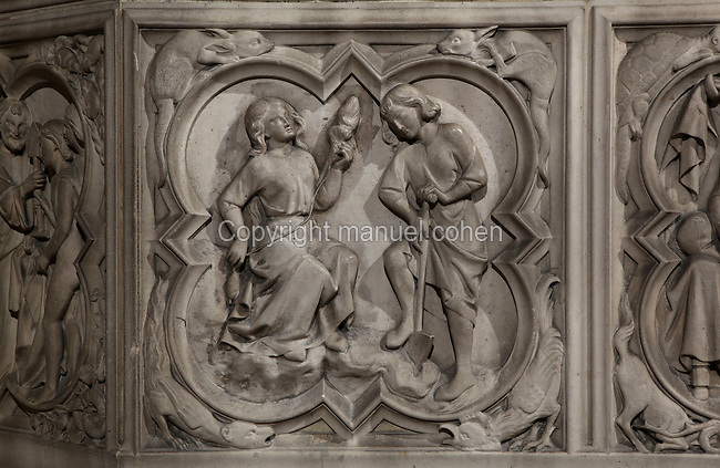Detail of bas-relief sculpture, mid 13th century, on the base of the portal of the Upper chapel of La Sainte-Chapelle, Paris, France. One of a series of reliefs illustrating scenes from the Old Testament book of Genesis. Here we see Adam digging the land and Eve spinning. Each panel has a decorated curly frame with mythical beasts in the corner. Sainte Chapelle was built 1239-48 to house King Louis IX's collection of Holy Relics. It is a UNESCO World Heritage Site. Picture by Manuel Cohen.
