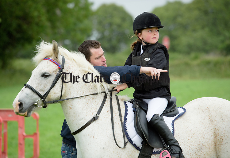 Former Clare hurling star Eamonn Taaffe, who scored a crucial goal for Clare in the 1995 All-Ireland final win against Offaly, briefs his daughter Anna before she competes on her pony Reggie at Tubber Horse Show. Photograph by John Kelly.