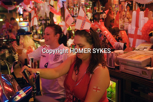 Bar maids pulling pints for English football fans, Southend on Sea, Essex. England. 2006
