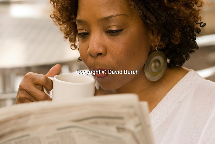 African American woman reading newspaper, thoughtful